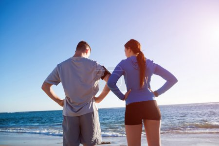 Photo for Young active couple of joggers on beach taking breath - Royalty Free Image