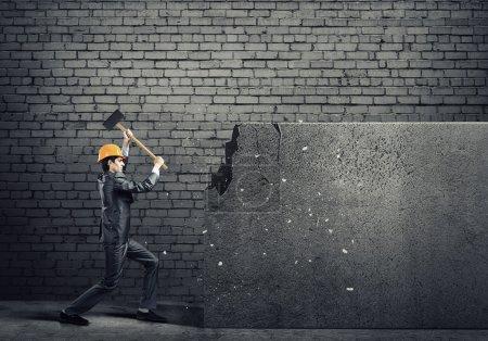 businessman in helmet breaking cement wall