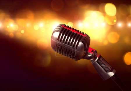 Photo for Close up of microphone in concert hall with blurred lights at background - Royalty Free Image