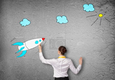 businesswoman drawing rocket
