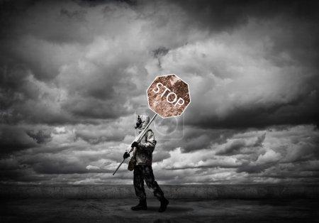 Photo pour Harceleur en masque à gaz avec panneau stop de précaution. Apocalypse et concept de catastrophe - image libre de droit
