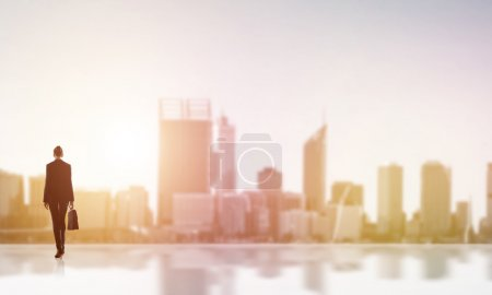 Photo for Rear view of businesswoman with suitcase looking at sunset above city - Royalty Free Image