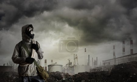 Photo for Man survivor in gas mask on industrial gray background. Horrible Post apocalyptic future - Royalty Free Image