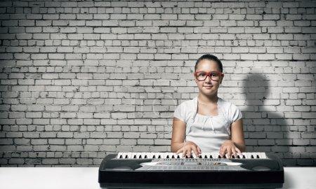 Photo pour Jolie écolière en lunettes rouges jouant du piano. Enfant fille jouer synthétiseur - image libre de droit