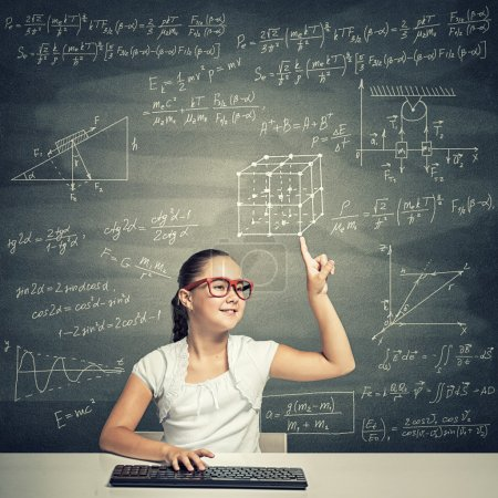 Photo for Girl of school age in red glasses sitting at table and typing on keyboard. Little school genius - Royalty Free Image