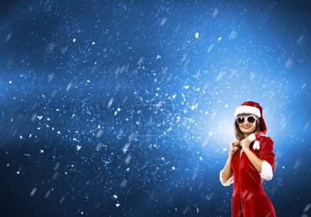 Photo for Young brunette woman in santa clothes on blue background - Royalty Free Image