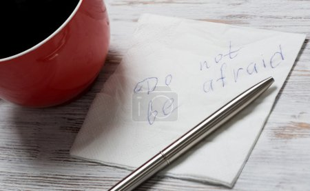 Photo for Cup of coffee and napkin with writings on table. Message written on napkin - Royalty Free Image