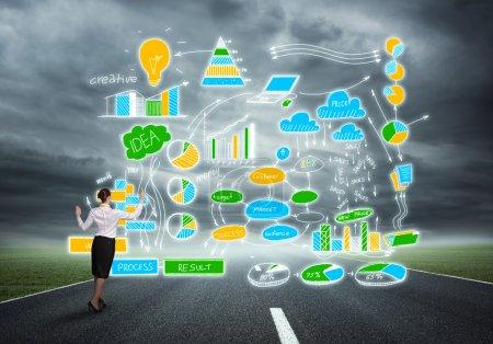 Photo pour Vue arrière de la femme d'affaires sur l'asphalte dessin de route croquis du plan d'affaires. Plan marketing réussi - image libre de droit