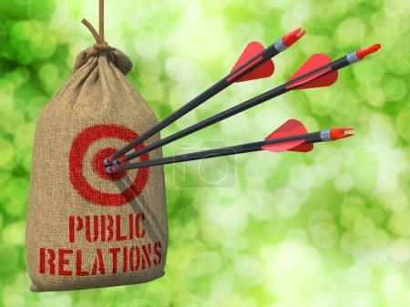 Photo pour Relations publiques - Trois flèches frappent une cible rouge sur un sac suspendu sur fond de bokeh vert . - image libre de droit