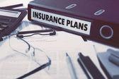 Insurance Plans on Ring Binder. Blured, Toned Image.