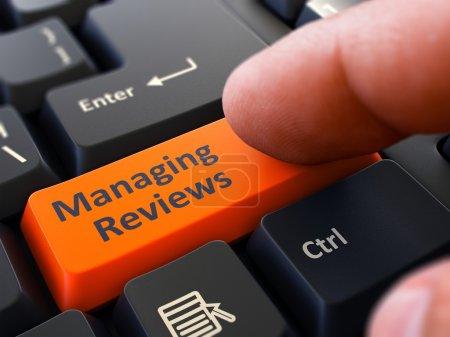 Pressing Orange Button Managing Reviews on Black Keyboard.