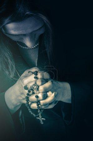 Photo pour Gros plan sur une femme prier avec un Rosaire sur ses mains - image libre de droit