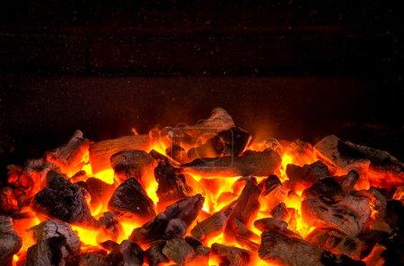 Photo pour Photo d'étincelles chaudes de charbons en feu dans un barbecue - image libre de droit