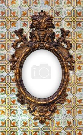 Photo pour Beau et complexe cadre baroque en laiton accroché à un mur carrelé - image libre de droit
