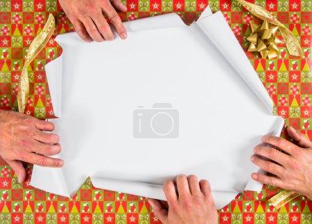 Photo pour Cadeau de Noël enveloppé ouvert par quatre mains - image libre de droit