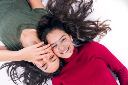 Photo for Two joyful teenager girls laying on the floor with their heads together - Royalty Free Image