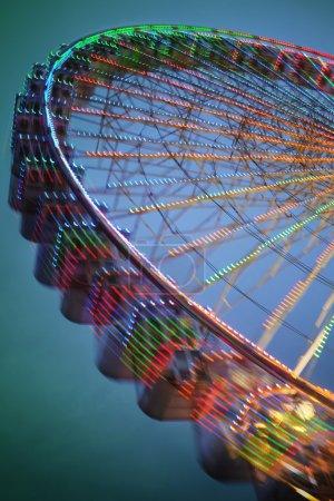 Photo pour Longue exposition sur une roue ferris mobile avec des lumières colorées - image libre de droit