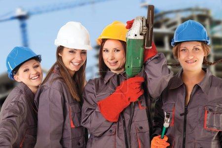 Photo pour Quatre femmes yung portant des vêtements de travail et des casques isolés avec un chemin de travail devant un arrière-plan de construction . - image libre de droit