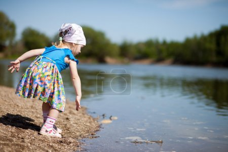 Photo for Little girl  in blue dress throwing stones into a lake - Royalty Free Image