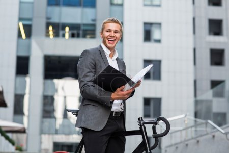 a young businessman standing on the steps of an office building, with a folder of papers and bike