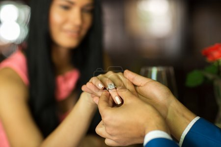 man making proposal to girlfriend in restaurant