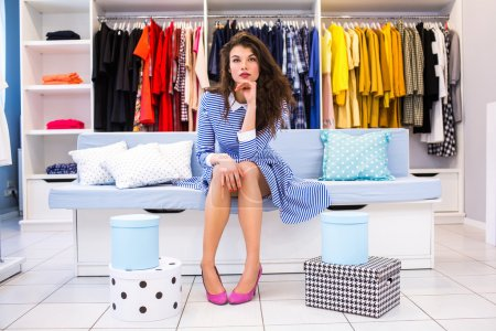 happiness, consumerism, sale and people concept - smiling young woman with shopping bags and box.He is sitting on a sofa in the store