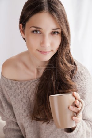 Photo for Beautiful woman drinking coffee in the morning sitting by the window - Royalty Free Image