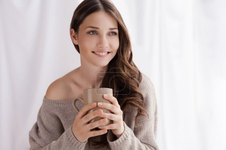 Beautiful woman drinking coffee, sitting by window