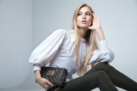 Photo pour Pleine longueur casual jeune femme à la mode assis avec un sac en arrière-plan léger - image libre de droit