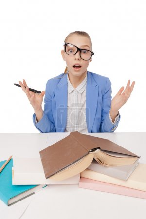 Photo pour Shocked, surprised student wearig glasses and sitting at desk with pen in hand in front pile books, studying, cant believe her eyes isolated over white background. Education. Face expression - image libre de droit