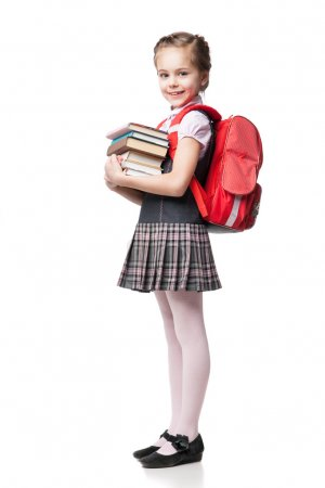 Cute smiling schoolgirl in uniform standing on white background and holding books