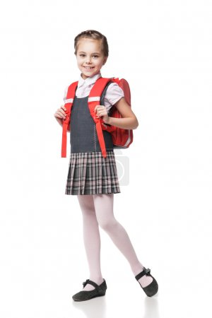 Cute smiling schoolgirl in uniform standing on white background