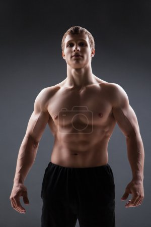 Muscular young man  shows the different movements and body parts