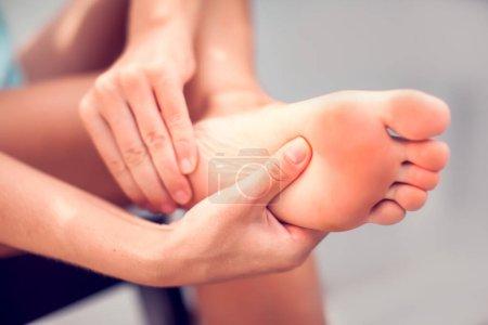 Schmerzen im Fuß, Mädchen hält ihre Hände an die Füße, Fußmassage, Krämpfe, Muskelkrämpfe, roter Akzent am Fuß, Nahaufnahme