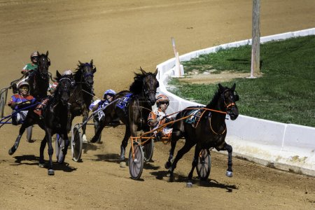 Group of five harness horses racing around turn on...