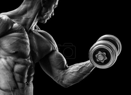 Photo for Handsome power athletic man in training pumping up muscles with dumbbell. Strong bodybuilder with six pack, perfect abs, shoulders, biceps, triceps and chest. Black and white image - Royalty Free Image