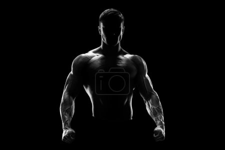 Photo for Silhouette of a strong fighter. Confident young fitness man with strong hands and clenched fists. Dramatic light. - Royalty Free Image