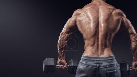 Strong bodybuilder doing exercises with dumbbells turned back