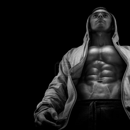 Photo for Bottom view of young strong bodybuilder showing off his physique against black background. Confident young fitness man with strong hands, abs and abdominal muscles. Dramatic light. - Royalty Free Image