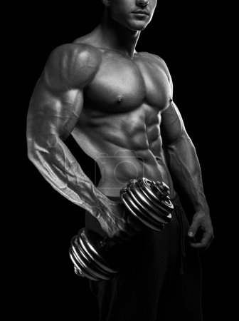 Photo for Handsome power athletic man with dumbbell confidently looking forward. Strong bodybuilder with six pack, perfect abs, shoulders, biceps, triceps and chest - Royalty Free Image