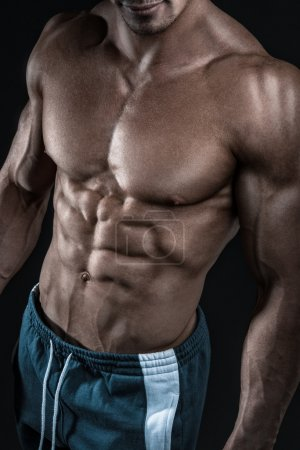 Strong athletic man fitness model showing torso muscles
