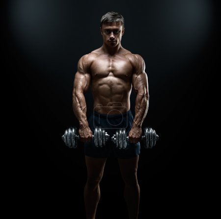 Photo for Handsome power athletic guy bodybuilder doing exercises with dumbbell. Fitness muscular body on dark background. - Royalty Free Image