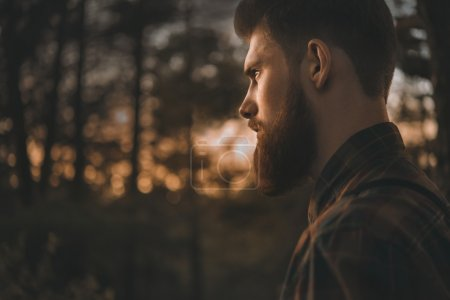 Photo for Brutal bearded man confidently looking forward. Standing alone in forest outdoor with sunset nature on background - Royalty Free Image