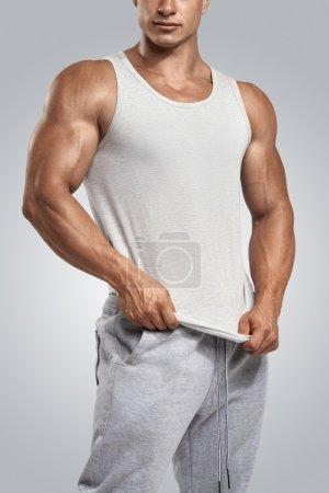 Young athlete wearing blank white vest, sleeveless t-shirt