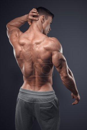 Photo pour Un bel homme athlétique a fait demi-tour. Isolé sur fond noir. bodybuilder fort avec épaules, biceps, triceps et poitrine - image libre de droit