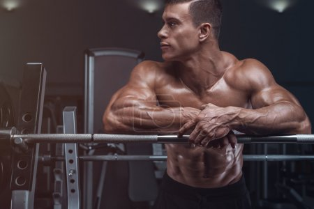Photo for Attractive muscular bodybuilder guy prepare to do exercises with barbell in a gym - Royalty Free Image