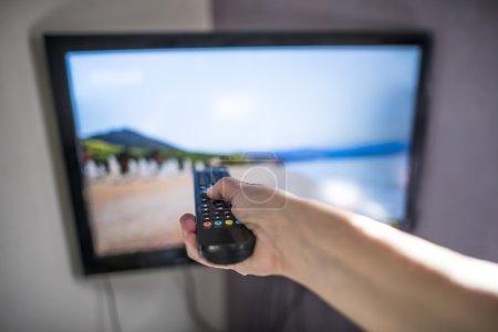 Photo pour TV et télécommande. Main tenant à distance. - image libre de droit