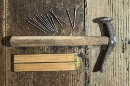 Vintage hammer, nails and wooden centimeter