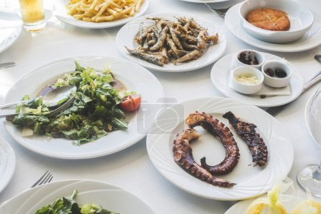 Table in greek restaurant. Salat and fish. Greece,...
