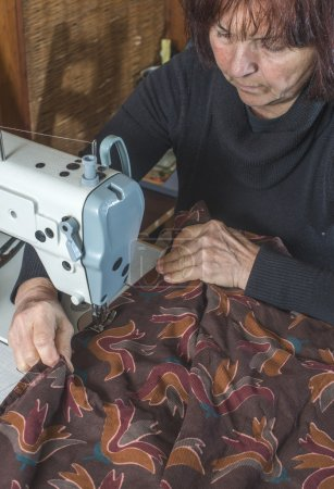 Woman sewing on sewing machine.